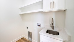 Pano Empty white laundry room with top storage, laundry connections and dryer vent on the wall