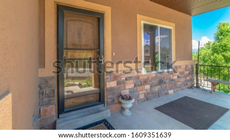 Pano Home exterior view with porch and glass door in front of the brown front door