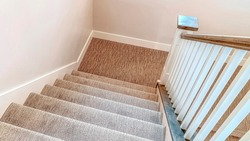 Pano Interior staircase with U shape design that leads to the basement of a home. The stairway has wooden handrails and carpet on the treads.