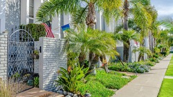 Pano Modern townhomes with landscaped yards stone fence and wrought iron gates. Narrow pathway, palm trees, and cloudy sky can be seen in this sunny residential scenery.