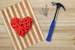 Pano picture with a heart made of threads and nails on a wooden board lies next to a hammer and nails