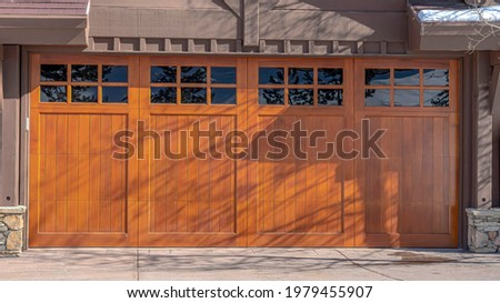 Pano Sunlit exterior of home in Park City Uta with glass paned brown garage door. The roof of the house is covered with snow on this sunny winter day. Stock fotó ©