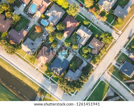 Panorama aerial vertical view residential houses with swimming pool in Carrollton, Texas, USA during fall sunset. Top view row of single-family homes with garden, driveway and attached garage