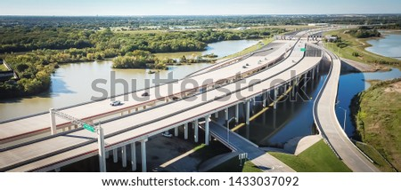 Panorama aerial view elevated highway viaduct through flood area near Dallas, Texas, USA. Top of multilevel expressway near a lake