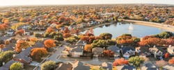 Panorama aerial view lakeside houses neighborhood with colorful autumn leaves. Flyover row of single-family houses with attached garage near lake with water fountain in Flower Mound, Texas, USA