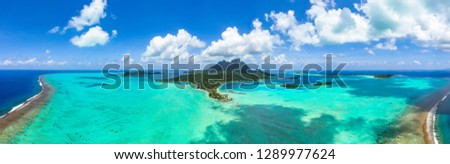 Panorama aerial view of Bora Bora island, Tahiti, French Polynesia, Matira point with overwater bungalows of a luxury resort and Mount Otemanu with amazing turquoise lagoon. Holiday dream. Paradise #1289977624