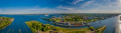 Panorama aerial view of the Kiel Canal waterway with lockage Holtenau. Cargo ships pass the Holtenau lock of the Kiel Canal. Industrial area at the Kiel Canal.