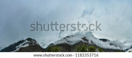 Panorama and a scene of beautiful and majestic mountainous mountains against the background of a cloudy sky with clouds streaking along the tops of the mountains. Altai, Siberia, Russia.