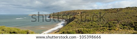 Panorama at Bells Beach, famous surfing destination in winter time, red cliffs, clouds, waves and hills from left break lookout in Victoria, Australia