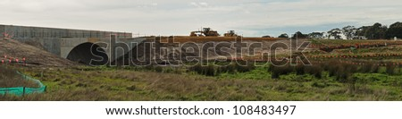 Panorama at bridge construction site for freeway with finished earthworks, bulldozers, red clay, clouds, trees and nature protection boundary marks in Victoria, Australia - stock photo