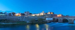 Panorama at night landscape of the city of Barcelos, district Braga, Portugal. Landscape on the river Cavado, Barcelos bridge, Paco dos Condes, water mill and church. Buildings all in stone