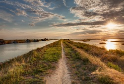 panorama at sunset of the wetland, a long straight pathway across the lagoon in the natural reserve Valli di Comacchio, near Ferrara, Emilia Romagna, Italy