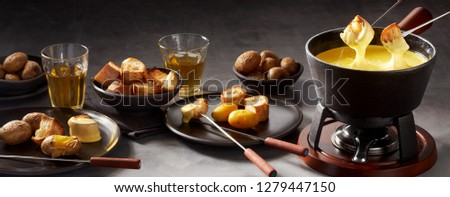 Panorama banner of a cheese fondue and sides with two forks with toasted bread being dipped in the sauce in a cast iron pot on a burner #1279447150