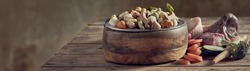 Panorama banner of healthy balanced food for your pet dog with a bowl filled with dried biscuits surrounded by fresh vegetable ingredients and bones with copyspace for advertising