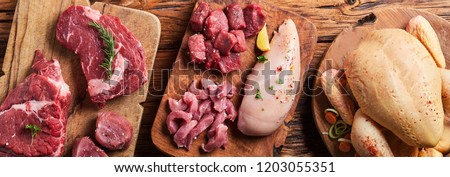 Panorama banner with an assortment of raw meats with a whole chicken, chicken breast, beef and pork on a rustic wooden table