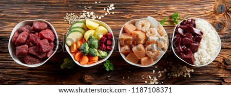 Panorama banner with healthy pet food ingredients with chopped raw beef, liver, chicken, vegetables, rice and grains in individual bowls on rustic wood viewed from above