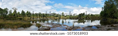 Photo of  Panorama Beautiful Background of Swamp, Flowing water, Waterfall or Puddle On the mountain. Among the forests and greenery. With nature Feeling relaxed and bright blue sky with cloud in background.