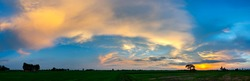 Panorama beautiful sunset with dark cloud over rice field in Thailand.blue sky with clouds.Fiery orange sunset sky. Beautiful sky.Sunrise with cloud over rice field.