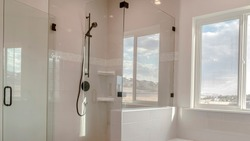 Panorama Built in bathtub with black faucet and shower stall with half glass enclosure