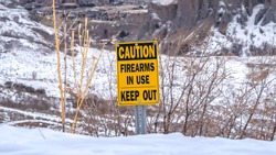 Panorama Caution Firearms In Use Keep Out sign on a mountain covered with snow in winter