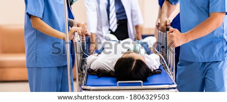 Panorama close up medical team of doctor and nurse push gurney stretcher with seriously injured patient with oxygen mask to the Operating Room. Emergency health care and medical hospital concept. Stockfoto ©