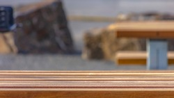 Panorama Close up of a light brown wooden table with benches at a park