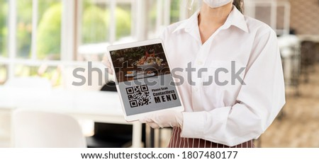 """Panorama close up waitress with face mask and face shield hold digital tablet with QR code for customer to scan for online contactless menu. QR Code is text """"Online Menu"""""""