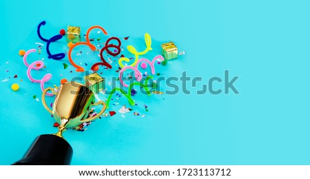 Panorama concept. Celebrating the success that has happened, Gold trophy placed on a blue background. There are gift boxes and colorful ribbons. Free space to put text into advertising media. Stock foto ©