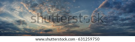 Panorama evening sky with blue, white and orange clouds.