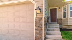 Panorama frame Garage door adjacent to concrete stairs that leads to the front door of a home