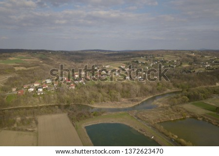Panorama from a bird's eye view. Central Europe: The Polish village is located among the green hills and river. Temperate climate. Flight drones or quadrocopter. Urbanization of the landscape.