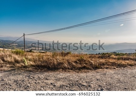 Panorama from mountain on desert in summer with yellow and brown colors of lands burned from the hot sun in Italy #696025132