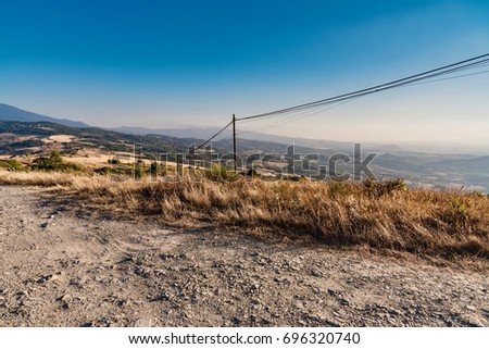 Panorama from mountain on desert in summer with yellow and brown colors of lands burned from the hot sun in Italy #696320740