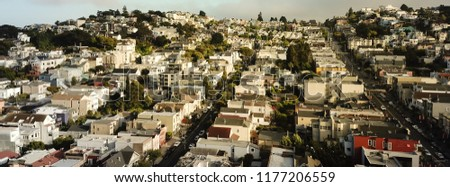 Panorama horizontal aerial view of The Castro District synonymous with gay culture in Eureka Valley. Flyover typical Victorian houses rolling hills cityscape, tightly packed residential homes