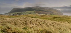 Panorama image of Knocknarea hill and Strandhill town in county Sligo, Ireland. cloudy sky, Green field with tall grass in foreground. Nobody.