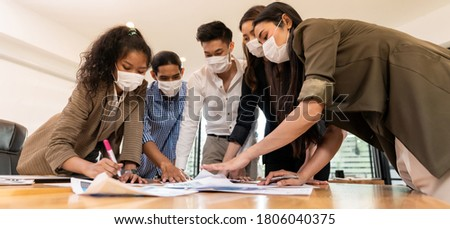 Panorama Interracial asian business team brainstorming idea at office meeting room after reopen due to coronavirus COVID-19. They wear face mask reduce risk to infection as new normal lifestyle.