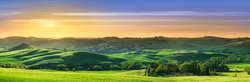 Panorama, Italian beautiful landscape, green rolling Tuscan fields in warm light of the setting sun