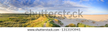 Panorama landscape coastline Dutch North Sea coast at IJmuiden during sunrise in warm clear light with low plain, dunes and wide beach with sea view against sky with scattered clouds #1313193941