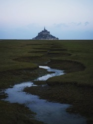 Panorama landscape view of Mont Saint Michel famous remote isolated island rock castle town in Normandy France Europe