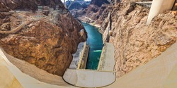 Panorama looking down the Colorado River from the Hoover Dam with both generator houses on each side of the blue water.