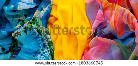 Panorama made of multi-colored fabric. Silk fabric for sewing light clothing. Three types of fabric create the background. Fashionable lightweight silk fabric.