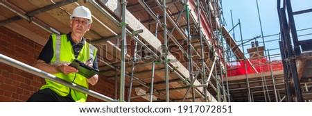 Panorama male builder foreman, construction worker, contractor or architect on building site writing on black clipboard panoramic web banner Foto stock ©