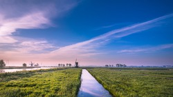 Panorama morning view of a typical Dutch landscape. With two windmills in the background.