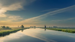 Panorama morning view of a typical Dutch landscape. With windmills and water and a bit of morning fog.