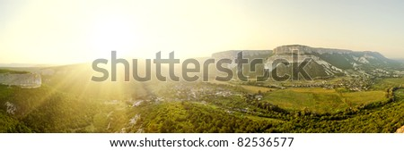 Panorama mountain area with green fields and vineyards