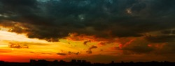 Panorama of a beautiful stormy sunset over the city in dramatic colors