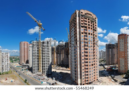 Panorama of a building site with a lot of residential high-rises under construction against beautiful summer sky.