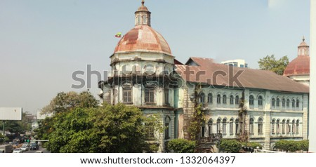 panorama of a busy street intersection in central Yangon, Myanmar, Southeast Asia, with traffic and old deteriorating British colonial buildings  stock photo