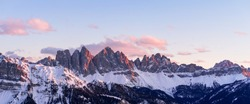 Panorama of a colored winter mountain landscape in South Tyrol, Italy during sunset in winter with the snow covered Seceda mountains.