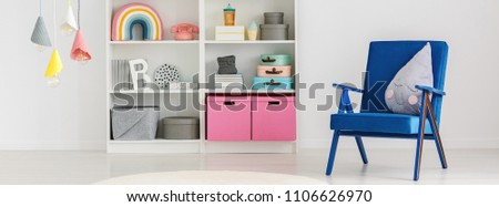 Panorama of a cute pillow on a blue armchair and a bookcase with boxes and decorations in a fun child bedroom interior with white walls #1106626970